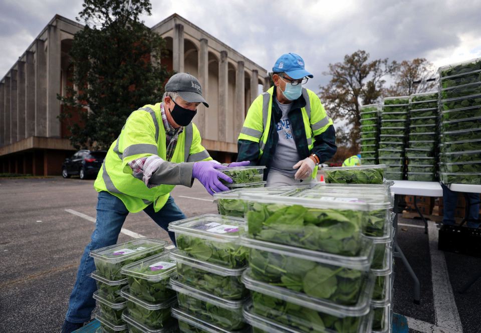 <strong>Pat Warren (left) stacks up hundreds of boxes of spinach to be given out to needy families at Lindenwood Church Nov. 14, 2020.</strong> (Patrick Lantrip/Daily Memphian)