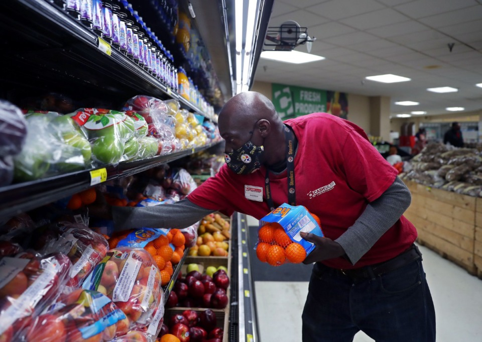 <strong>Andrew Brodnax stocks the shelves at Cash Saver's Midtown location Dec. 20, 2020.</strong> (Patrick Lantrip/Daily Memphian)
