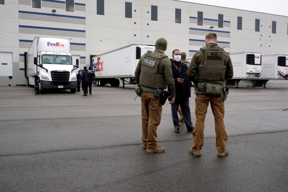 <strong>U.S. Marshals stand near FedEx trucks parked at the loading dock outside the McKesson distribution center in Olive Branch, Miss., Sunday, Dec. 20, 2020.</strong> (Paul Sancya/AP)