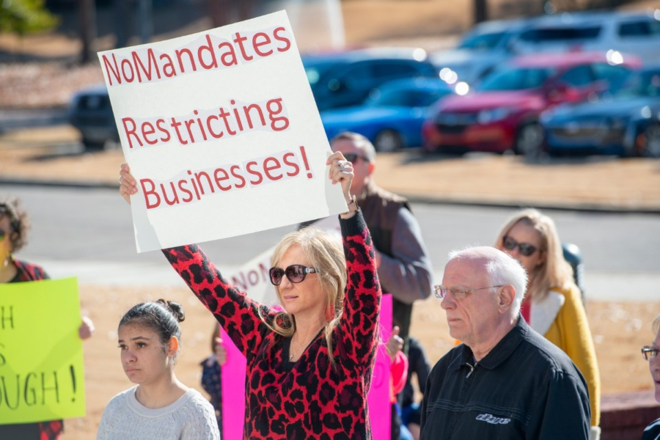 <strong>Debbi Robbins Wood with Conservative Women of Collierville holds a sign in protest of the Shelby County Health Department&rsquo;s mandates. Several business owners and citizens gathered at the Collierville Town Hall to voice their opposition.</strong> (Greg Campbell/Special to the Daily Memphian)