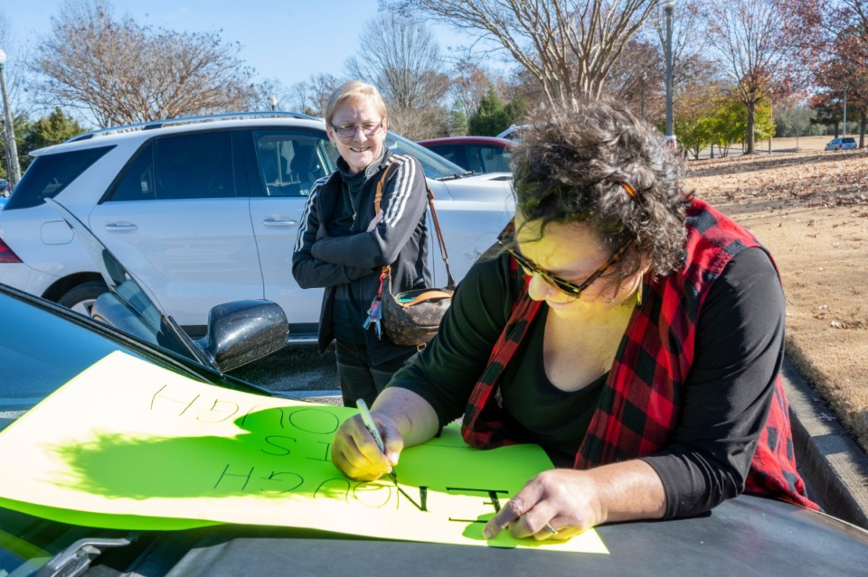 <strong>Karen Shelton, owner of Simply Done Catering in Collierville, prepares a sign for a protest Monday at the Collierville Town Hall. Protester Chandler Peterson watches.</strong> (Greg Campbell/Special to the Daily Memphian)