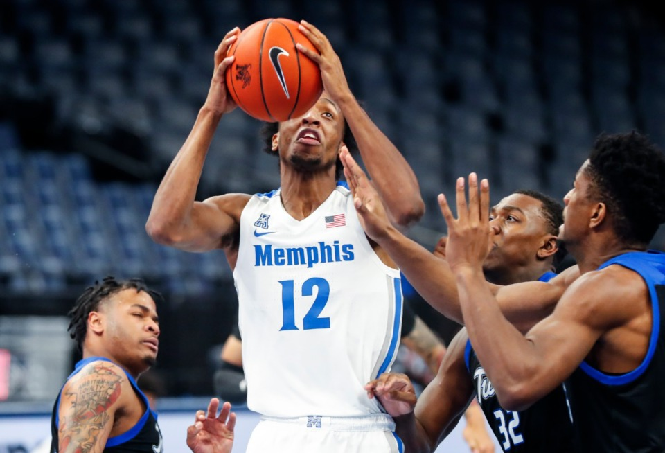 <strong>Memphis forward DeAndre Williams (middle) drives the lane against the Tulsa defense during action on Monday, Dec. 21, 2020.</strong> (Mark Weber/The Daily Memphian)