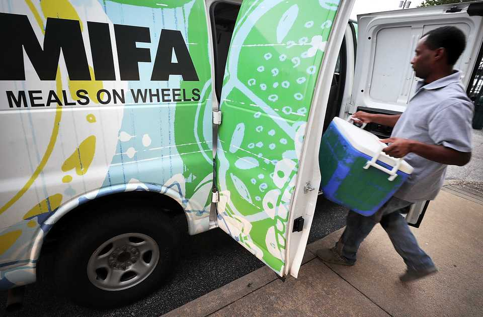 <strong>MIFA employee loads up meals for one of the organizations collection points on Thursday August 16, 2018. Fueled by thousands of volunteers, MIFA, which turns 50 this year, has gone high tech with pre-plotted routes and an app, but deliveries are still made with a personal touch. </strong>(Jim Weber/Daily Memphian)