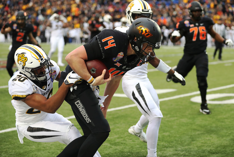 <strong>Oklahoma State quarterback Taylor Cornelius (14) takes a hit as he rolls to the right looking for a first down in the second quarter of the AutoZone Liberty Bowl on Dec. 31, 2018. Cornelius, a walk-on at Oklahoma State, was awarded Most Valuable Player honors after his Liberty Bowl performance.</strong> (Patrick Lantrip/Daily Memphian)