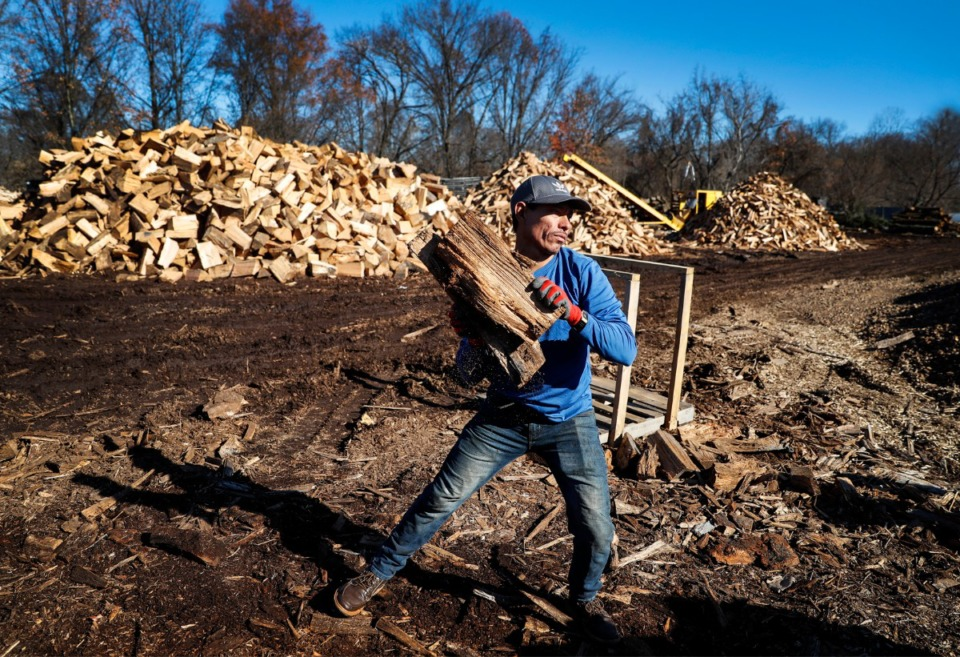 <strong>With more people staying at home due to the pandemic, more firewood is being used. At Woodland Tree Service, employee Jos&eacute; Barrios tosses freshly cut firewood that will be stacked to dry on Tuesday, Dec. 22, 2020. </strong>(Mark Weber/The Daily Memphian)
