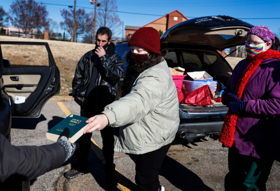 <strong>Lunches &rsquo;N Love outreach ministries&rsquo; founder Sydney Crabtree (middle) hands out a Bible while giving donated supplies to the needy on Friday, Dec. 25, 2020 around Downtown.</strong> (Mark Weber/The Daily Memphian)