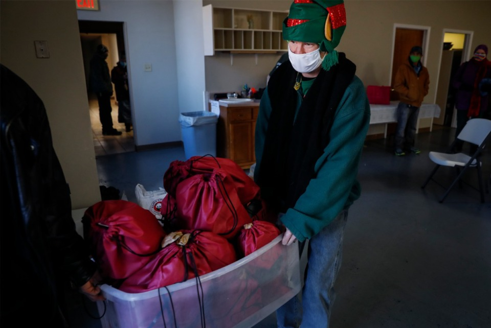 <strong>Lunches &rsquo;N Love outreach ministries&rsquo; volunteer Joe Morris wears a festive hat while carrying supplies to be handed out to the needy on Friday, Dec. 25, 2020.</strong> (Mark Weber/The Daily Memphian)