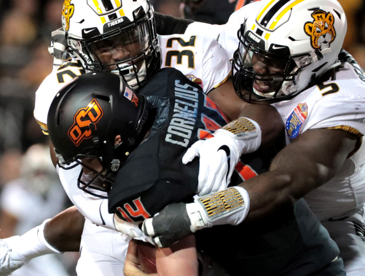 <strong>Oklahoma State Cowboys quarterback Taylor Cornelius (14) gets sacked by University of Missouri Tigers linebacker Nick Bolton (32) and defensive lineman Terry Beckner Jr. (5) during the AutoZone Liberty Bowl game on Dec. 31, 2018. The Cowboys won 38-33.</strong> (Houston Cofield/Daily Memphian)