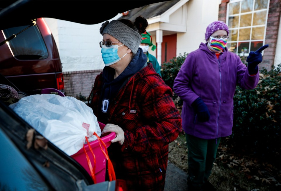 <strong>Lunches &rsquo;N Love outreach ministries&rsquo; volunteers Robin Gordon (left) and Lori Morris (right) load their cars with supplies that will be handed out to the needy on Friday, Dec. 25, 2020.</strong> (Mark Weber/The Daily Memphian)