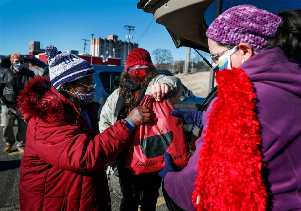 <strong>Lunches &rsquo;N Love outreach ministries&rsquo; founder Sydney Crabtree (middle) hands supplies to the needy on Friday, Dec. 25, 2020 around Downtown</strong>. (Mark Weber/The Daily Memphian)