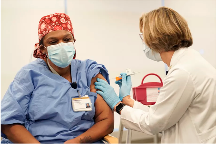 "<span class=""e-image__meta""><strong>Tesha Akins, who works directly with COVID patients at Vanderbilt University Medical Center in Nashville, receives the hospital&rsquo;s first coronavirus vaccination from nurse Robin Steaban on Thursday, Dec. 17, 2020.</strong> (Photo provided by Chalkbeat Tennessee)<br /></span>"