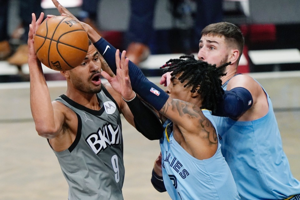 <strong>Brooklyn Nets guard Timothe Luwawu-Cabarrot (9) looks to pass the ball over Grizzlies guard Ja Morant (12) and center Jonas Valanciunas (17) on Monday, Dec. 28, 2020, in New York.</strong>&nbsp;<strong>Later on Morant left the game in a wheelchair, and Twitter lit up.</strong> (Kathy Willens/AP)