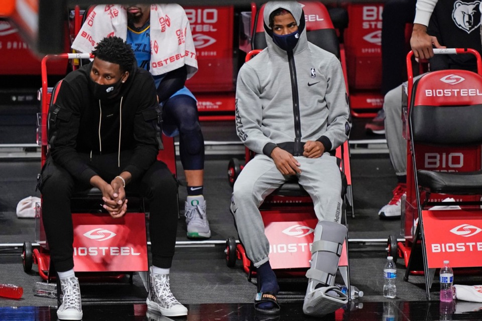 <strong>Grizzlies guard Ja Morant, right, sits on the sideline in his sweats with a boot on his left foot after suffering an injury during the game against the Brooklyn Nets on Monday, Dec. 28, 2020, in New York.</strong> (Kathy Willens/AP)