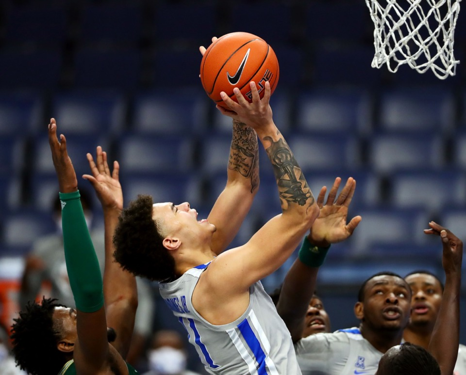 <strong>University of Memphis guard Lester Quinones (11) fights through a foul during a home game against the University of South Florida on Dec. 29, 2020.</strong> (Patrick Lantrip/Daily Memphian)