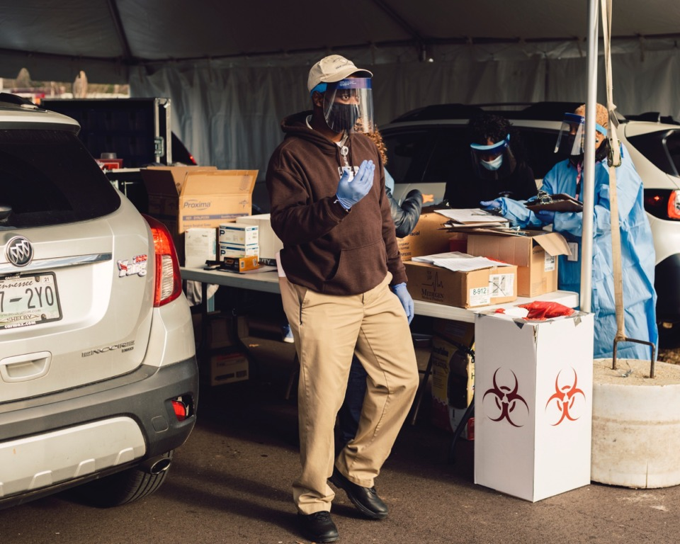 <strong>A health care worker ushers a line of vehicles through a coronavirus vaccination site. Health care and essential workers were among the first to receive the vaccine on Monday, December 28, 2020</strong>. (Houston Cofield/Special To The Daily Memphian)