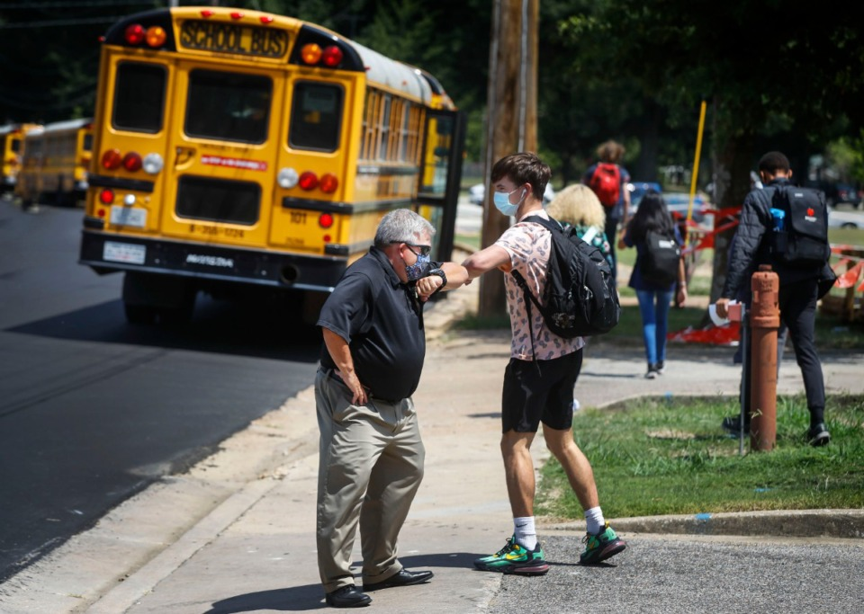 <strong>Millington High School teacher Hank Hawkins (left) elbow bumps students as they head home after the first day of classes on Monday, Aug. 10. Due to the pandemic, Millington students will return to school virtually next week.</strong>&nbsp;(Mark Weber/Daily Memphian file)