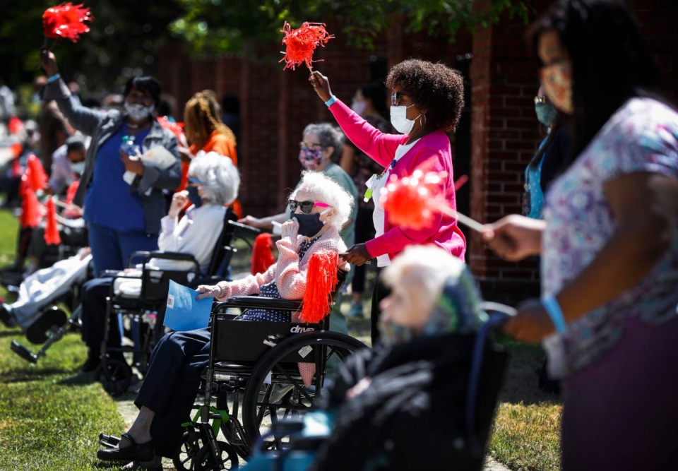 <strong>Assisted living and skilled nursing residents from Trezevant Manor wave to family members, who paraded by them in April</strong>. (Houston Cofield/Special To The Daily Memphian)