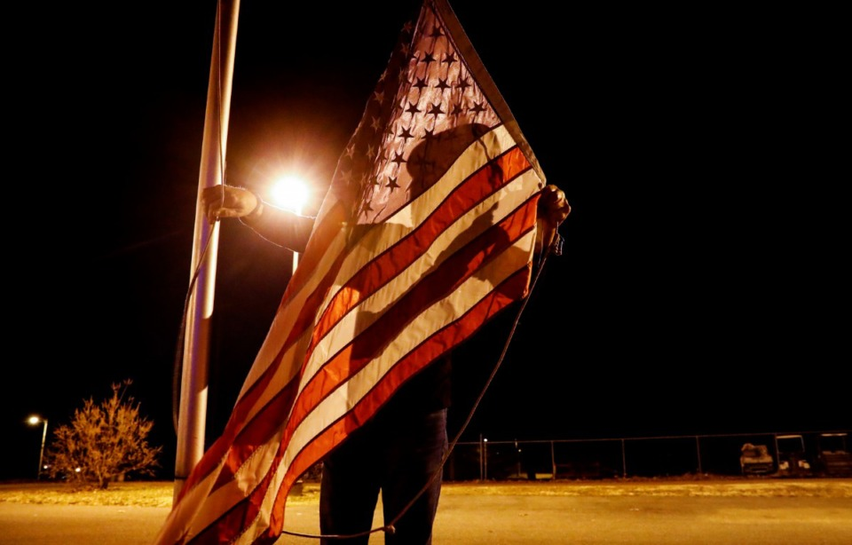 <strong>Navy veteran Chris Oldham raise the flag before sunrise on Monday, Dec. 28, 2020 at Alpha Omega Veterans Services&rsquo; facility on Ball Street.</strong> (Mark Weber/The Daily Memphian)