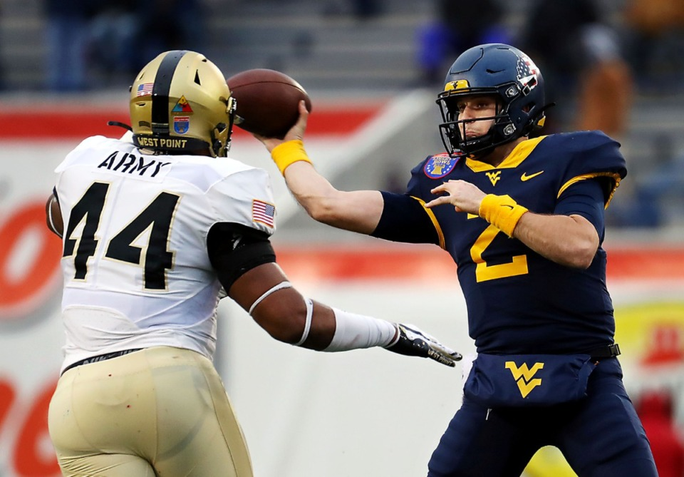<strong>University of West Virginia quarterback Jarrett Doege (2) throws a pass while under duress by Army linebacker Nathaniel Smith (44) at the AutoZone Liberty Bowl on Dec. 31, 2020.</strong> (Patrick Lantrip/Daily Memphian)