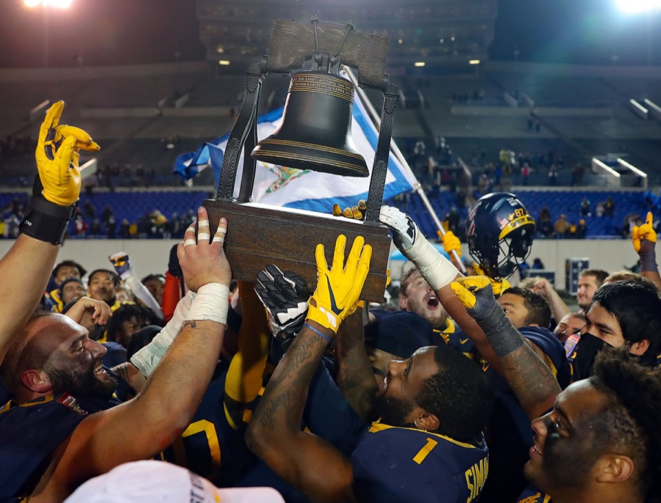 <strong>University of West Virginia players hoist the Liberty Bowl trophy after beating Army 24-21 in the AutoZone Liberty Bowl on Dec. 31, 2020.</strong> (Patrick Lantrip/Daily Memphian)