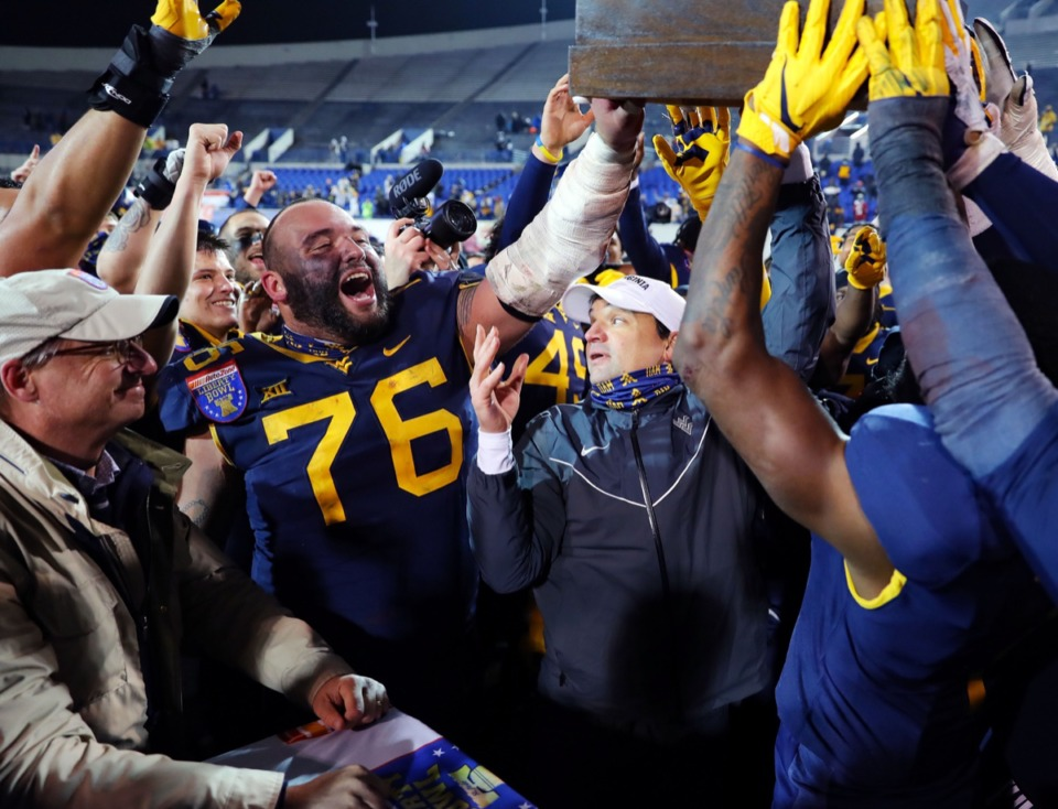 <strong>University of West Virginia coach Neal Brown hoists the Liberty Bowl trophy with his players after beating Army 24-21 in the AutoZone Liberty Bowl on Dec. 31, 2020.</strong> (Patrick Lantrip/Daily Memphian)