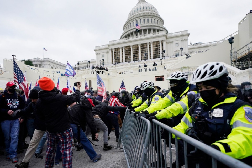 <strong>Trump supporters try to break through a police barrier on Wednesday, Jan. 6, at the Capitol in Washington. As Congress prepared to affirm President-elect Joe Biden's victory, thousands of people gathered to show their support for President Donald Trump and his claims of election fraud.</strong> (Julio Cortez/Associated Press)
