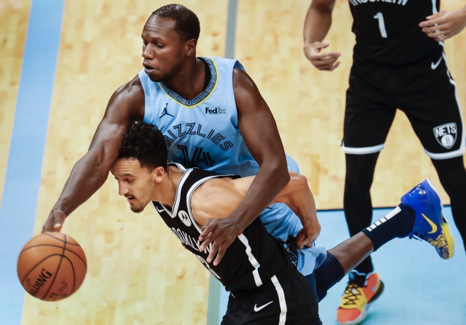 <strong>Grizzlies center Gorgui Dieng (top) tries to save the ball from going out of bounds while battling Brooklyn&rsquo;s Landry Shamet (bottom) on Friday, Jan. 8, 2021.</strong> (Mark Weber/The Daily Memphian)