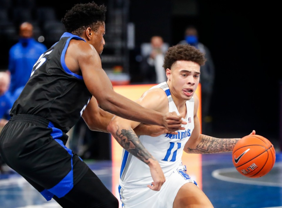 <strong>Memphis guard Lester Quinones (left) drives the lane against the Tulsa defense during action on Monday, Dec. 21, 2020.</strong> (Mark Weber/The Daily Memphian)