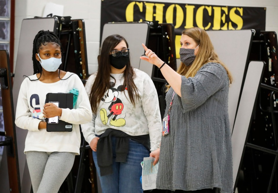 <strong>Returning Arlington High School ninth grade students Chandon Garrett (left) and Neola Bice (middle) talk with Ellen Payne (right) on the restrictions due to COVID-19 protocols on Thursday, Jan. 7, 2021.</strong> (Mark Weber/The Daily Memphian)