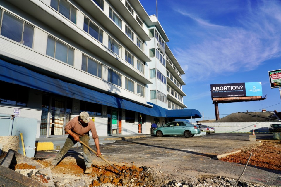 <strong>Pedro Patino works Wednesday, Jan. 13, to remove a wall between the parking lots of 2600 Poplar Place (behind him) and RockHouse Live at 2586 Poplar.</strong> (Tom Bailey/Daily Memphian)