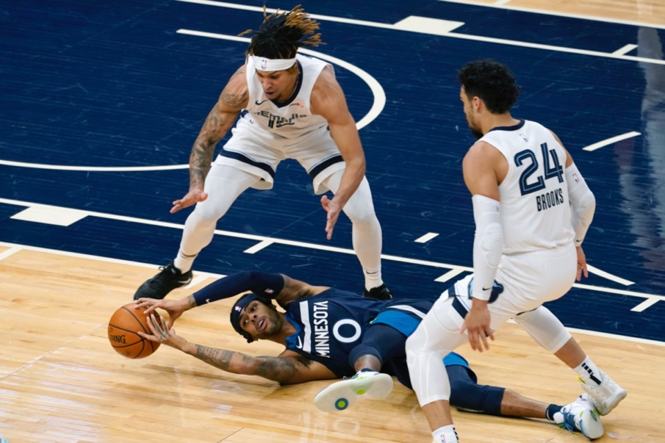<strong>Minnesota Timberwolves' D'Angelo Russell (0) tries to grab the ball after falling while double-teamed by Memphis Grizzlies' Brandon Clarke and Dillon Brooks on Wednesday, Jan. 13, 2021, in Minneapolis.</strong> (Jim Mone/AP)
