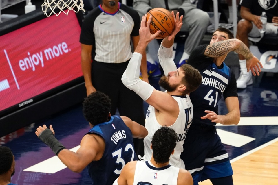 <strong>Memphis Grizzlies' Jonas Valanciunas shoots past Minnesota&rsquo;s Karl-Anthony Towns (32) and Juancho Hernangomez (41) on Wednesday, Jan. 13, 2021, in Minneapolis. The Grizzlies won 118-107. Valanciunas led the Grizzlies with 24 points.</strong> (Jim Mone/AP)