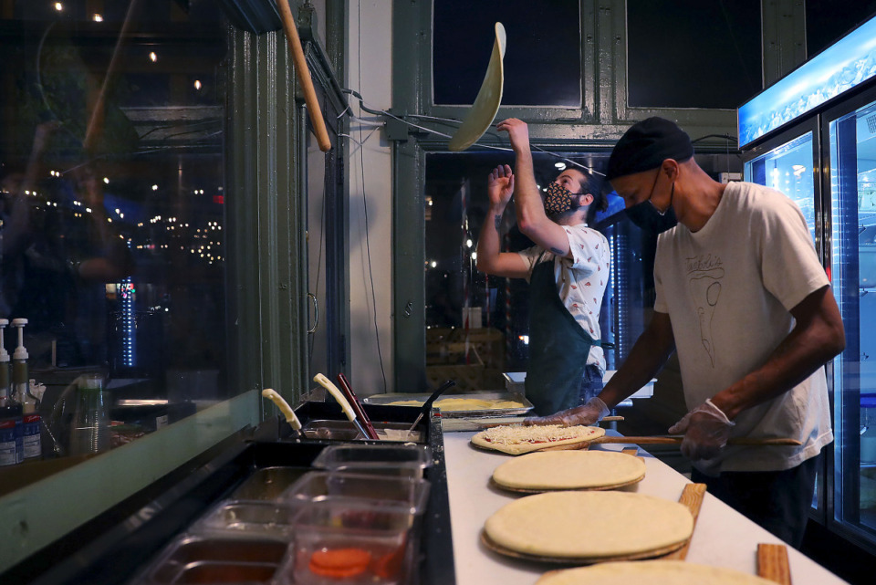 <strong>Miles Tamboli (left) tosses pizza dough in the air while Carlus Perry preps pizzas at Tamboli's Pasta &amp; Pizza in Midtown Jan. 13, 2021.</strong> (Patrick Lantrip/Daily Memphian)