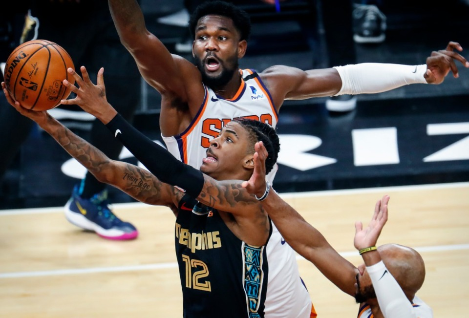<strong>Memphis Grizzlies guard Ja Morant (bottom) drivers for a layup against Phoenix Suns defender Deandre Ayton (top) during action on Monday, Jan. 18, 2021.</strong> (Mark Weber/The Daily Memphian)