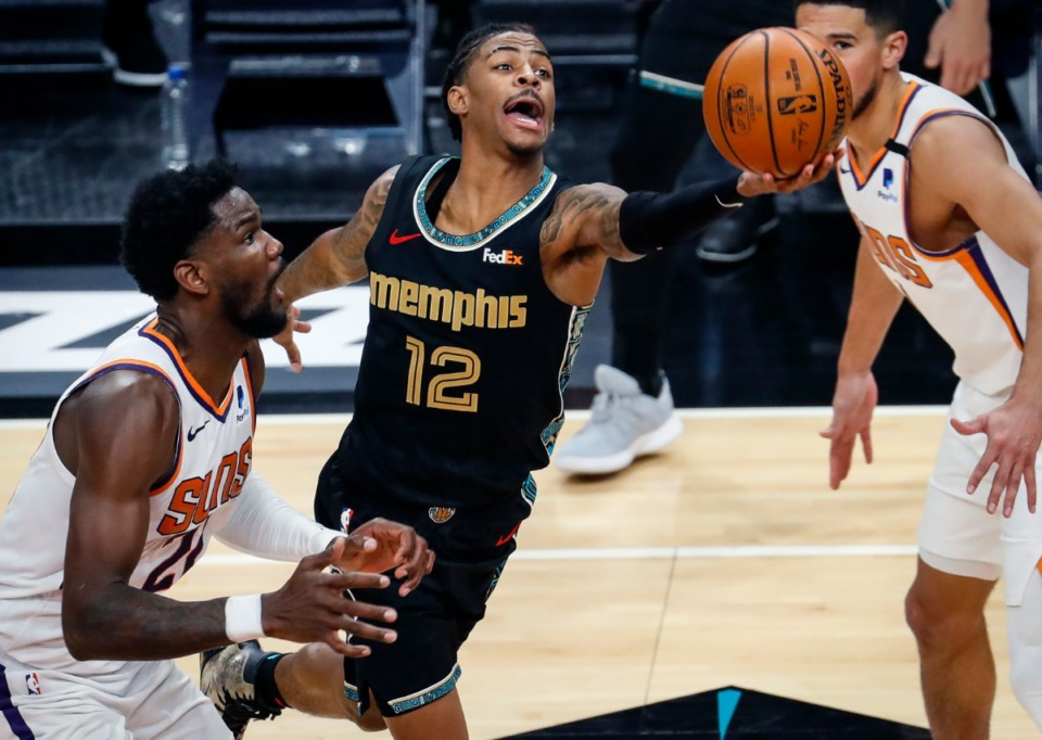 <strong>Memphis Grizzlies guard Ja Morant (middle) drives for a layup in front of Phoenix Suns defender Deandre Ayton (left) during action on Monday, Jan. 18, 2021.</strong> (Mark Weber/The Daily Memphian)