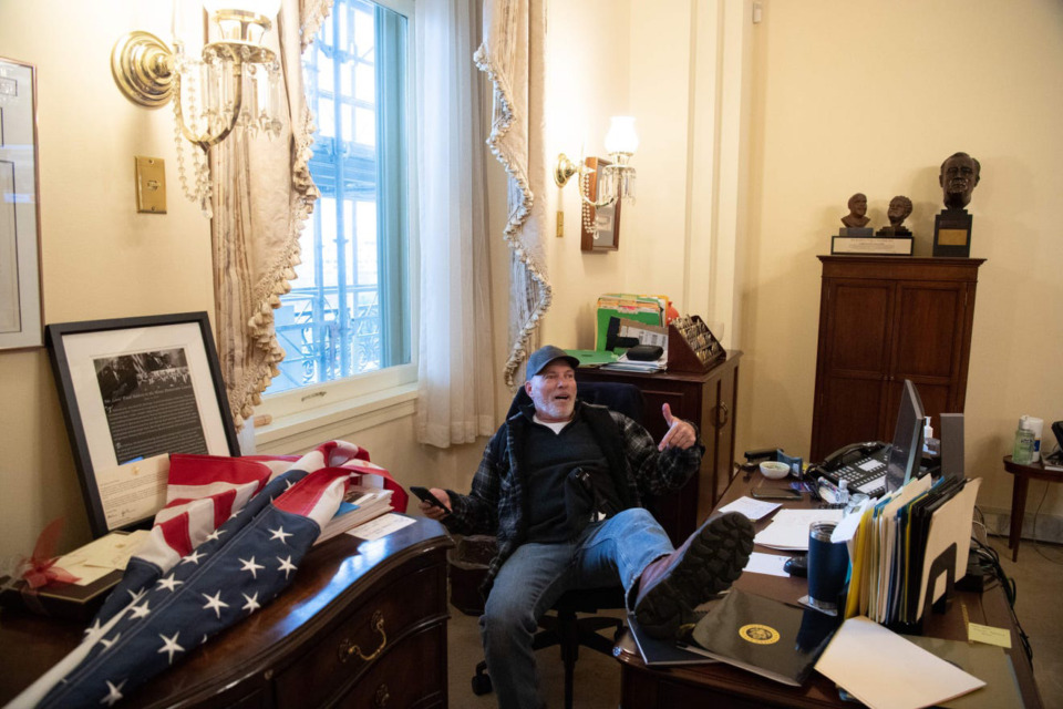 <strong>Richard Barnett sits at a desk in House Speaker Nancy Pelosi&rsquo;s office during the Jan. 6 Capitol attack.</strong> (U.S. District Court for Western Arkansas records)