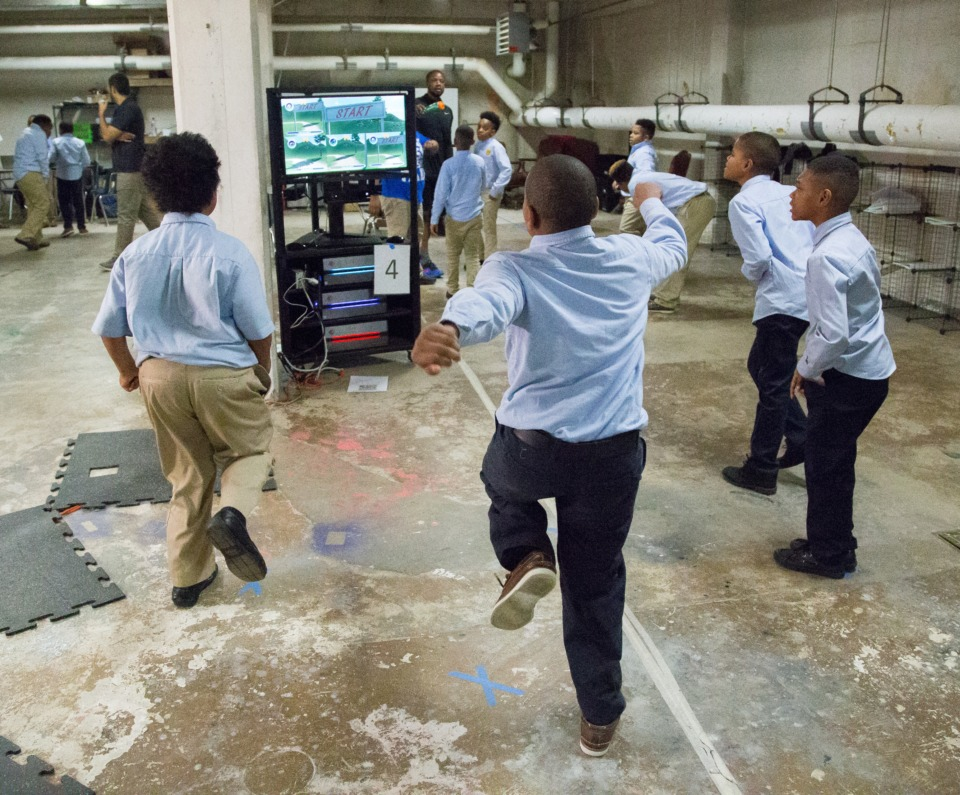 <strong>Students at Memphis Grizzlies Preparatory Charter School did not have dedicated gym space, so Fit4Class enables up to 30 students to exercise together in smaller spaces. The children follow on-screen characters to learn stationary exercises such as jump squats. A combination of cameras track students movements to correlate with on-screen characters.</strong> (Troy Glasgow)