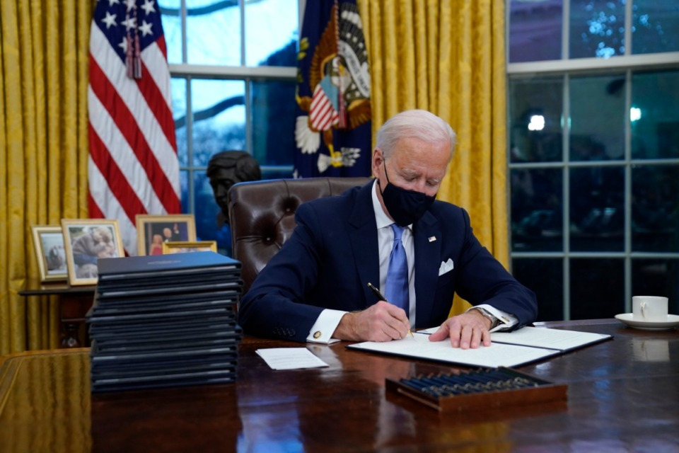 <strong>President Joe Biden signs executive orders in the Oval Office of the White House on Wednesday, Jan. 20, in Washington.</strong>&nbsp;(Evan Vucci/Associated Press)