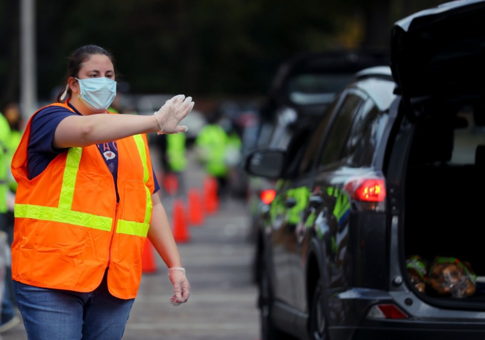 <strong>Alana Wells (in a Nov. 14, 2020 file photo) directed traffic as hundreds of cars lined up to pick up food donations at Lindenwood Christian Church in Midtown. &ldquo;This pandemic has widened the gulf between the &lsquo;haves&rsquo; and &lsquo;have-nots&rsquo;,&rdquo; letter writer&nbsp;Rev. Dr. Dorothy Sanders Wells says.</strong> (Patrick Lantrip/Daily Memphian)