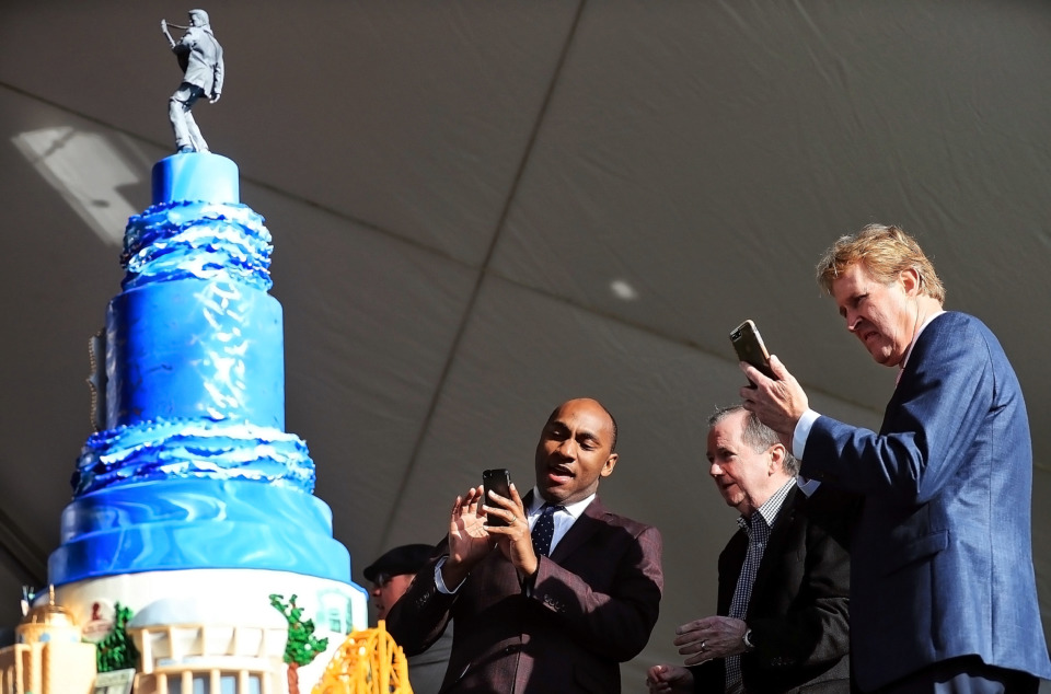 <strong>Shelby County Mayor Lee Harris (left), EPE CEO Jack Soden and Kevin Kane of the Memphis Convention &amp; Visitors Bureau grab a couple quick shots of the cake as Elvis fans gather at Graceland on Jan. 8, 2019, to celebrate the King of Rock &rsquo;n' Roll's 84th birthday.</strong> (Jim Weber/Daily Memphian)