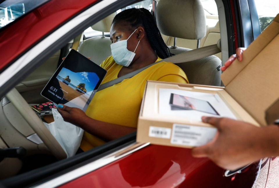 <strong>Woodstock Middle School parent Erica Eulls looks over digital tablets and keyboards issued to her children by Shelby County Schools on Monday, Aug. 3, 2020, at Trezevant Career and Technology Center.</strong> (Mark Weber/Daily Memphian file)