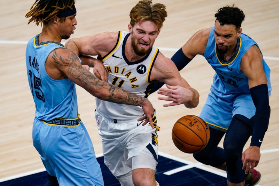 <strong>Indiana Pacers forward Domantas Sabonis (11) is fouled as he drives between Memphis Grizzlies forward Brandon Clarke (15) and guard Dillon Brooks (24) in Indianapolis, Tuesday, Feb. 2, 2021.</strong> (Michael Conroy/AP)