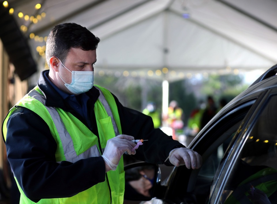<strong>Reece Halyard with the Collierville Fire Department administers a COVID-19 vaccine at Germantown Baptist Church's new drive-thrui location on Feb. 2, 2021.</strong> (Patrick Lantrip/Daily Memphian)