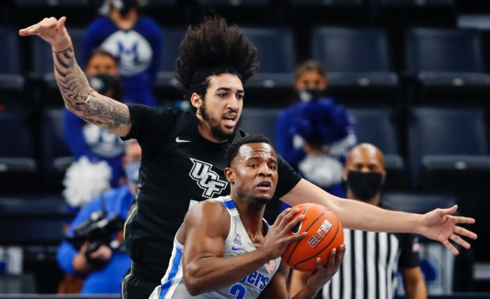 <strong>Guard Alex Lomax (front) grabs a rebound in front of UCF forward Avery Diggs (back) on Wednesday, Feb. 3, 2021.</strong> (Mark Weber/The Daily Memphian)
