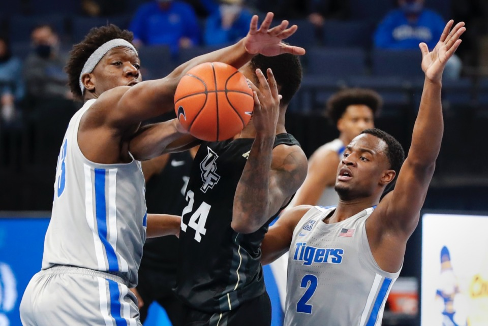 <strong>Tigers Malcolm Dandridge (left) and Alex Lomax (right) close a defensive trap on UCF forward Dre Fuller Jr. (middle) on Wednesday, Feb. 3, 2021.</strong> (Mark Weber/The Daily Memphian)