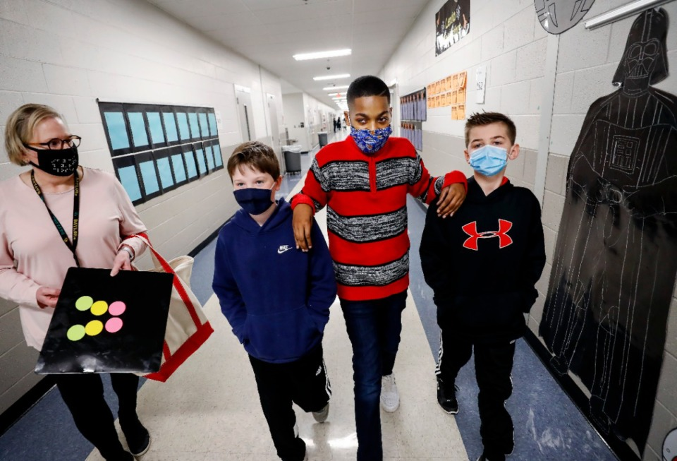 <strong>Aalando Perry is guided by his classmates and best friends Cade Vanzant (left) and Hudson Talbot (right) as vision specialist Lou Harber walks with them on Thursday, Feb. 4, at Tara Oaks Elementary.</strong> (Mark Weber/Daily Memphian)