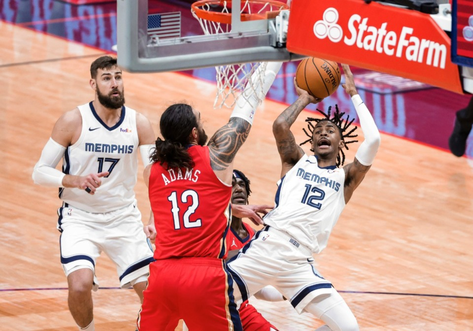 <strong>Memphis Grizzlies guard Ja Morant (12) shoots over New Orleans Pelicans center Steven Adams (12) and guard Kira Lewis Jr. during the third quarter of an NBA basketball game in New Orleans, Saturday, Feb. 6, 2021.</strong> (Derick Hingle/AP)