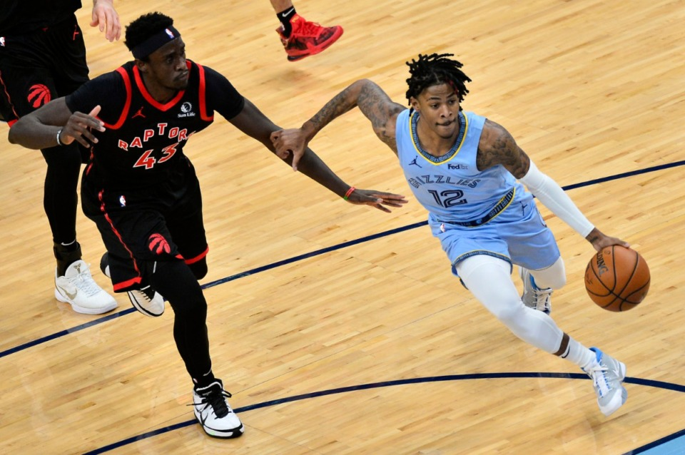 <strong>Memphis Grizzlies guard Ja Morant (12) drives ahead of Toronto Raptors forward Pascal Siakam (43) on Feb. 8, 2021, at FedExForum.</strong> (Brandon Dill/AP)
