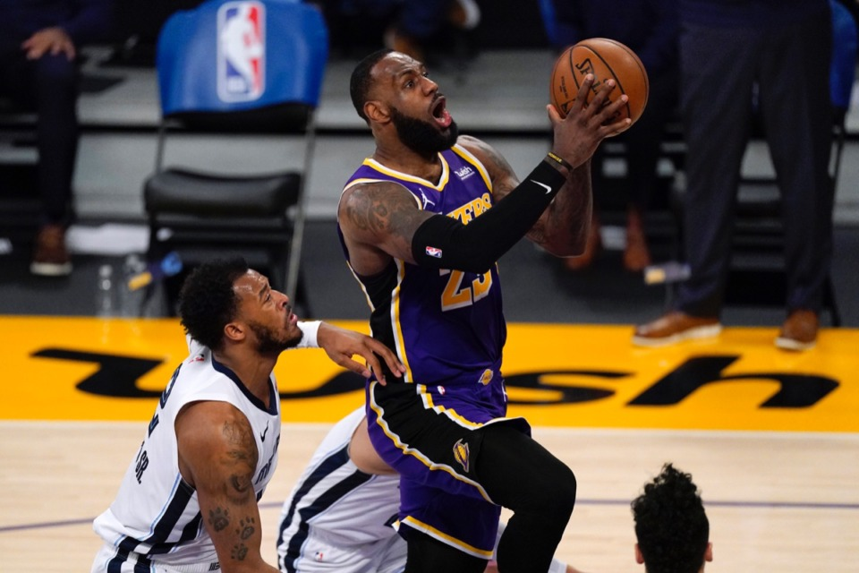 <strong>Lakers forward LeBron James, right, goes to the basket in front of Memphis Grizzlies center Xavier Tillman Sr. on Feb. 12, 2021, in Los Angeles.</strong> (Mark J. Terrill/AP)