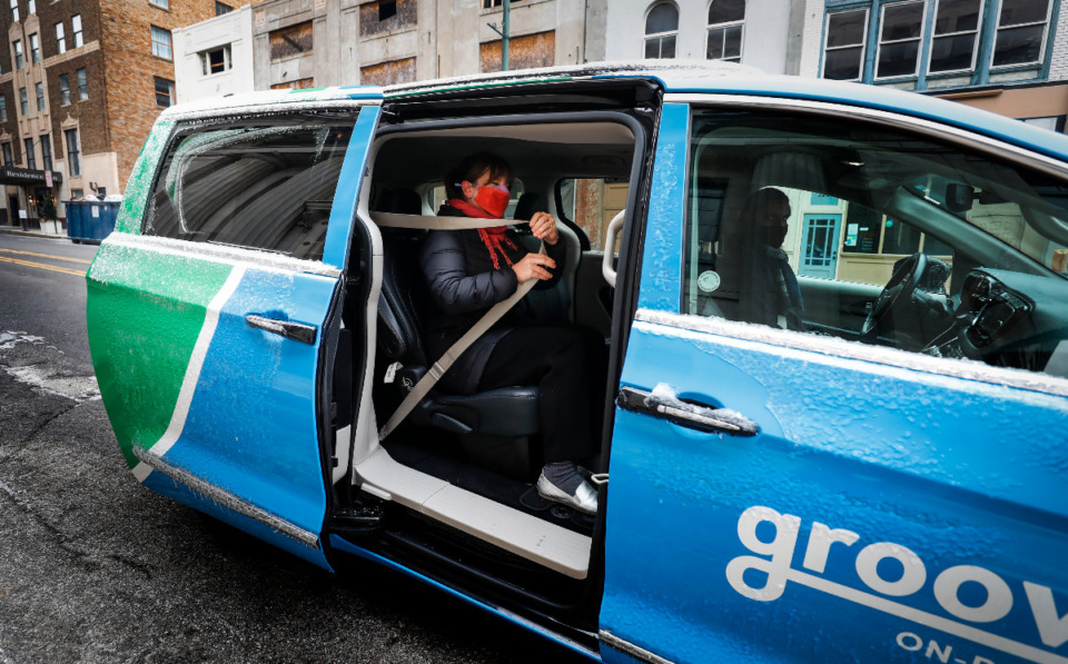 <strong>Lauren Crabtree, with Downtown Memphis Commission, puts on her seatbelt while grabbing a ride from Groove On-Demand on Friday, Feb. 12, 2021 in Downtown Memphis. Crabtree, who doesn&rsquo;t own a car and is getting married next weekend, needed to pick up her wedding shoes near the Crosstown Concourse area.</strong> (Mark Weber/The Daily Memphian)